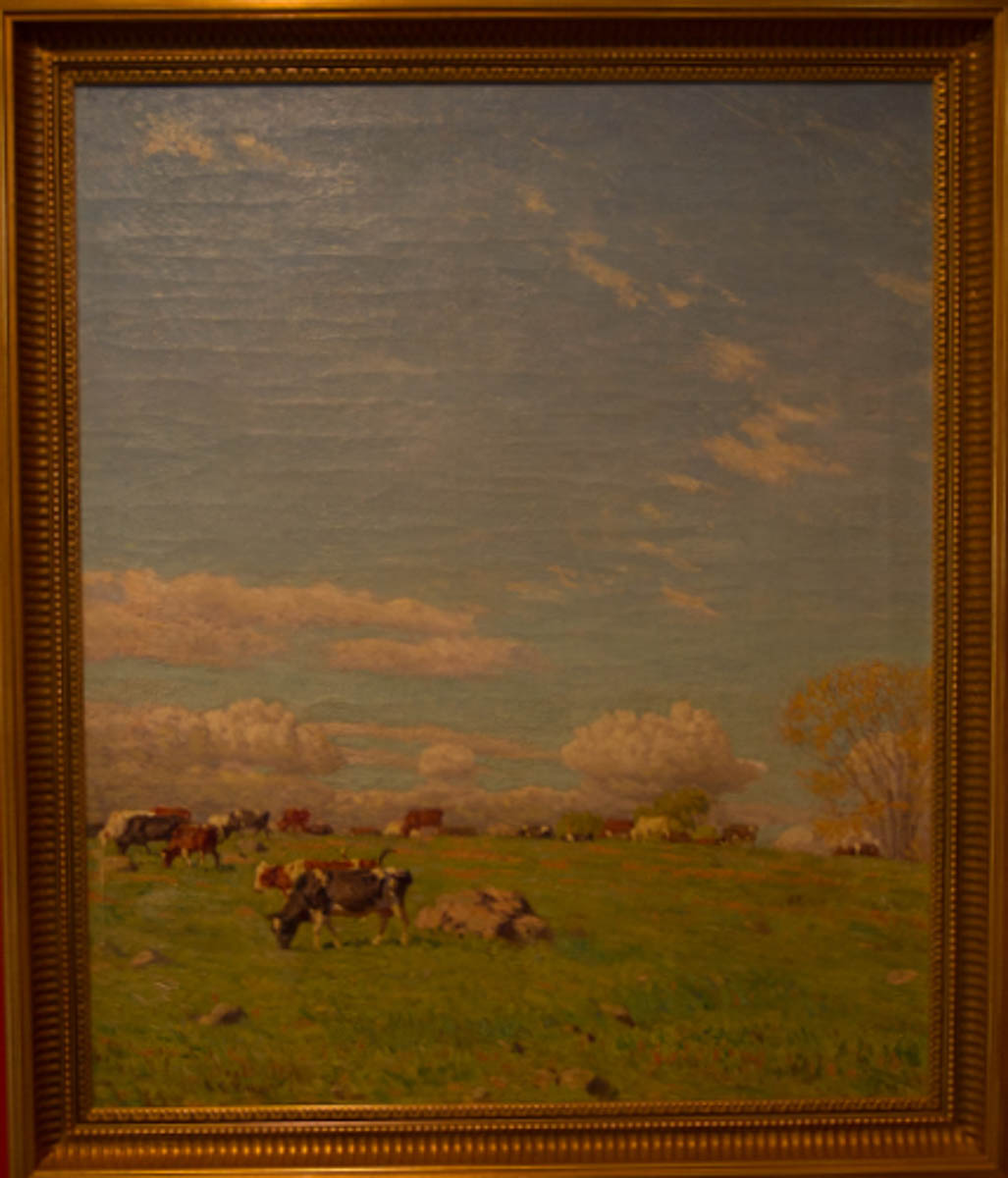 Untitled [Small cows grazing against a tall sky]